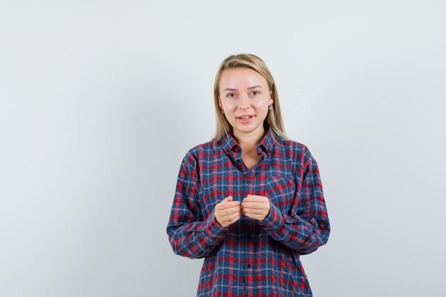 Блондинка женщина, взявшись за руки, играет на консоли в клетчатой рубашке и выглядит оптимистично. передний план.