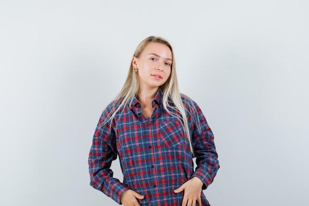 Donna bionda che tiene le mani sulla pancia, che propone alla macchina fotografica in camicia controllata e che sembra affascinante. vista frontale.