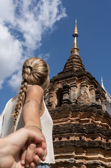 Blonde woman holding hands in front of a buddhist temple