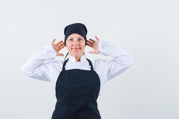 Блондинка женщина держит руки возле уха в черной форме повара и выглядит красиво, вид спереди.