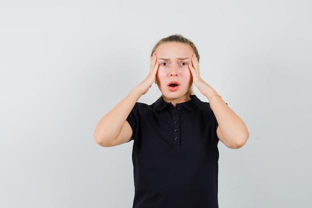 Donna bionda che tiene le sue mani sulla sua testa con la bocca aperta in maglietta nera e che sembra infastidita