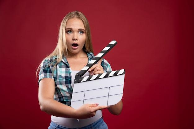 Donna bionda in possesso di un ciak di produzione cinematografica e sembra confusa e stanca.