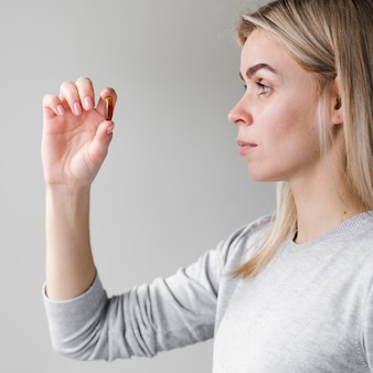 Blonde woman holding pill