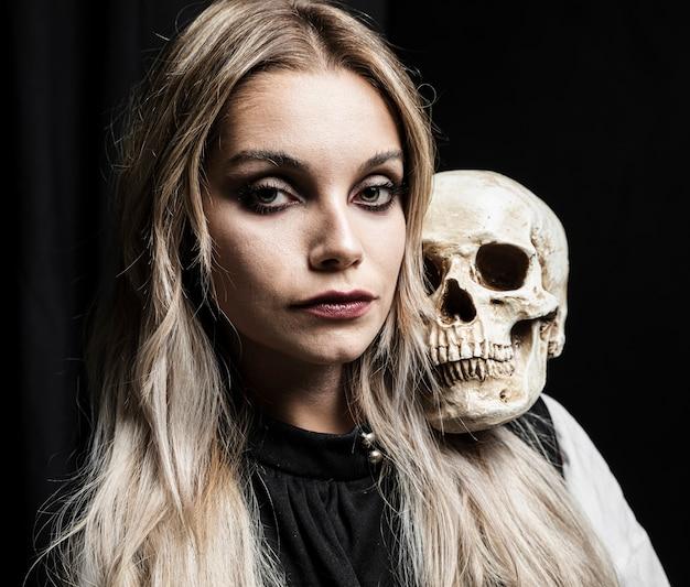 Blonde woman holding skull on shoulder