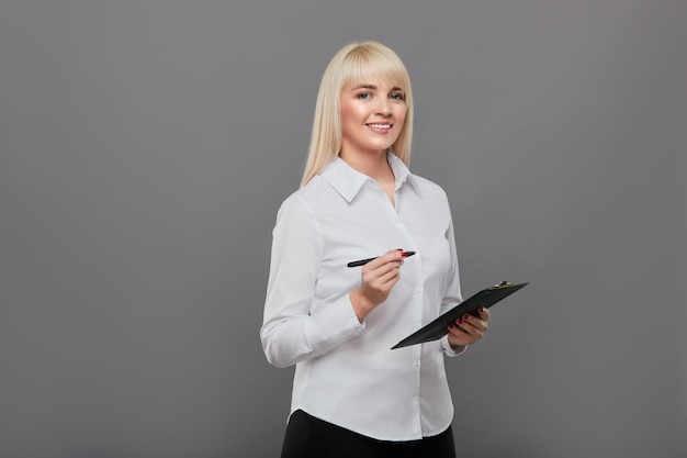 Blonde woman holding tablet making questionnaire.