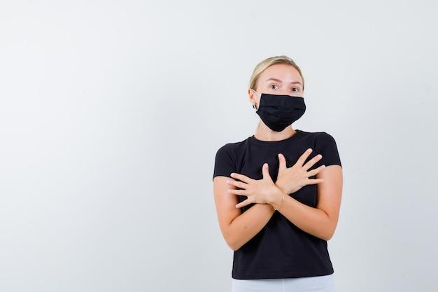 Donna bionda con due braccia incrociate sul petto in maglietta nera