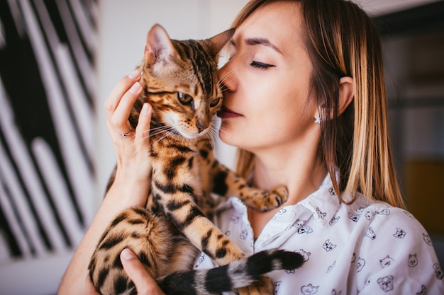 La donna bionda tiene un gatto del bengala