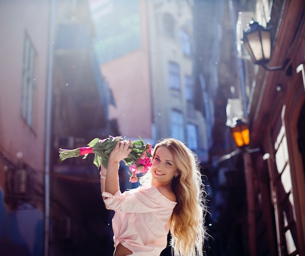 Blonde woman holds a bouquet of pink peonies posing on the street