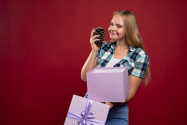 金髪の女性は手に樫の木の円錐形を持っており、前向きで楽しいように見えます。