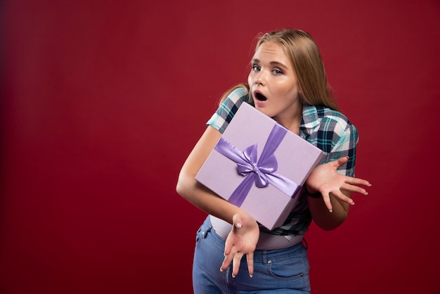 Blonde woman holds tight a gift box and gets jealous about sharing.