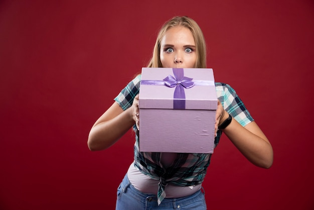 Blonde woman holds tight a gift box and looks confused and dissatisfied.