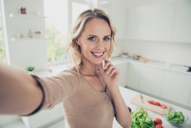 Blonde woman at home in the kitchen with vegetables