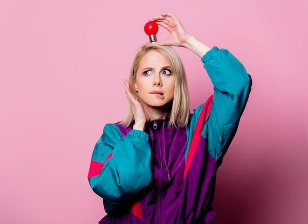 ピンクの壁に電球と90年代のスポーツスーツのブロンドの女性