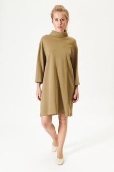ベージュのポロネックドレスを着た金髪の女性