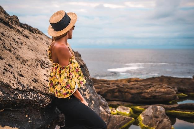 岩の多いビーチで花柄のシャツを着た金髪の女性