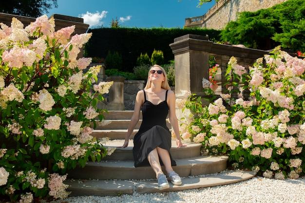 Блондинка в саду с цветами гортензии