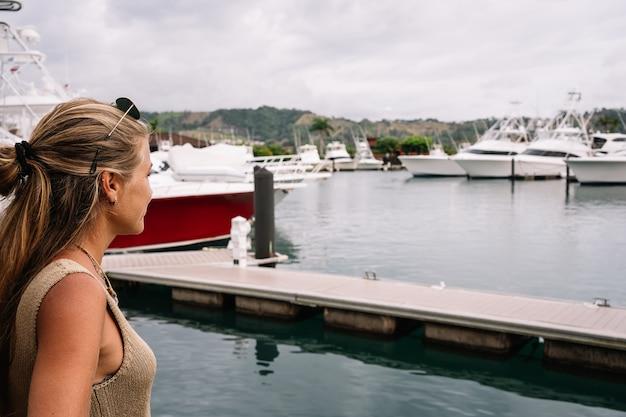係留されたヨットを見ている港のブロンドの女性