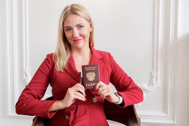 Блондинка в красном платье держит национальный паспорт гражданина рф