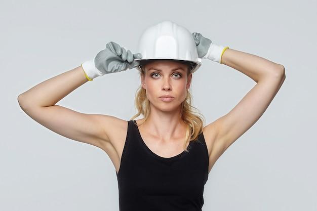 금발의 여자. 흰색 보호 헬멧에. 건설 개념