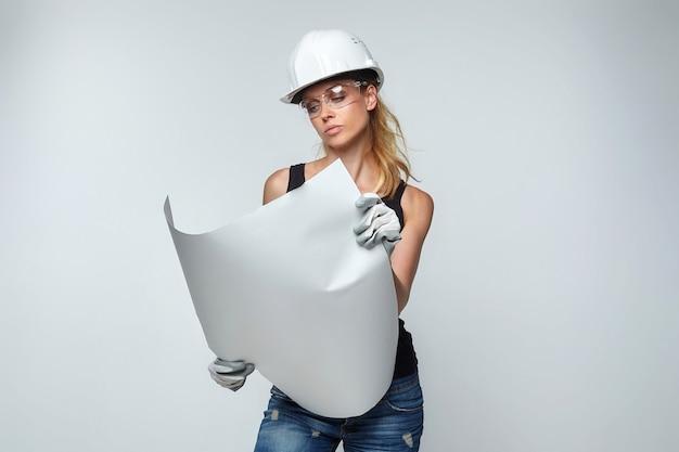 금발의 여자. 흰색 보호 헬멧에 그의 손에 프로젝트가 있습니다. 건설 개념