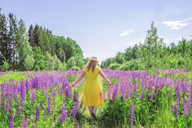 Блондинка в желтом платье в поле люпина. летний солнечный день.