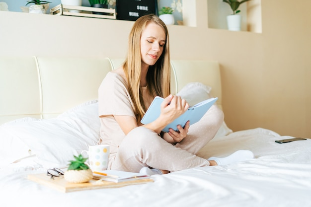 Блондинка в постели с книгой