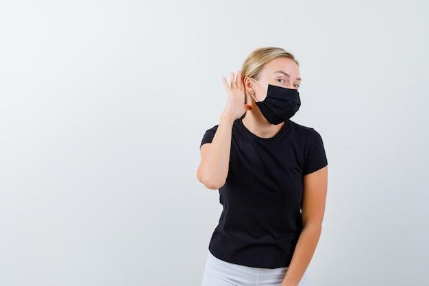 黒のtシャツ、白いズボン、耳の近くで手を握って黒いマスクのブロンドの女性
