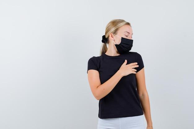 黒のtシャツ、白いズボン、胸に手を保持している黒いマスクのブロンドの女性