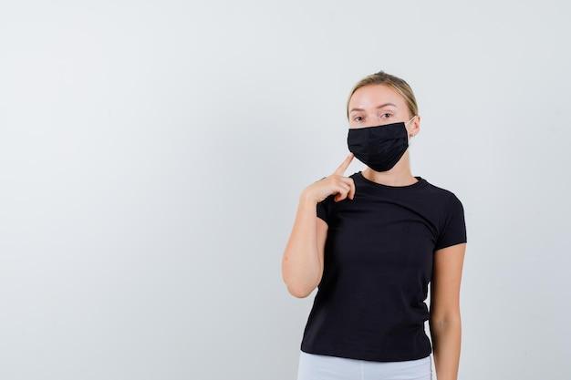 黒のtシャツ、白いズボン、人差し指を保持している黒いマスクのブロンドの女性