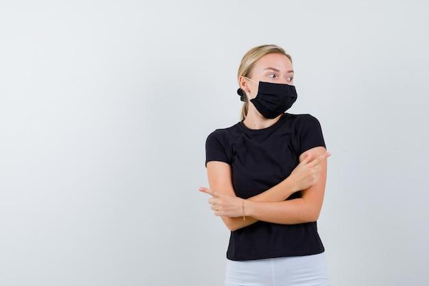 黒のtシャツ、白いズボン、2本の腕を組んで黒いマスクのブロンドの女性