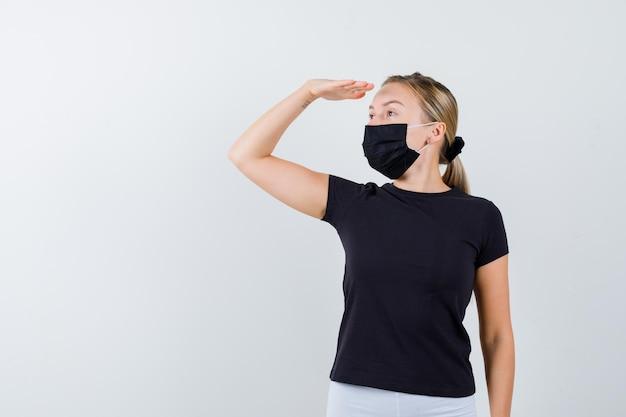 黒のtシャツ、白いズボン、遠くを見ている黒いマスクのブロンドの女性