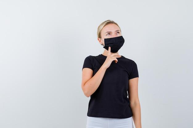 黒のtシャツ、白いズボン、あごに人差し指を置く黒いマスクのブロンドの女性