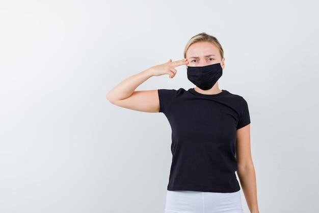 黒のtシャツ、白いズボン、頭の近くで銃のジェスチャーを示す黒いマスクのブロンドの女性