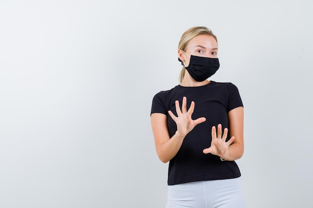 검은 티셔츠, 흰색 바지, 정지 신호를 보여주는 검은 마스크에 금발 여자