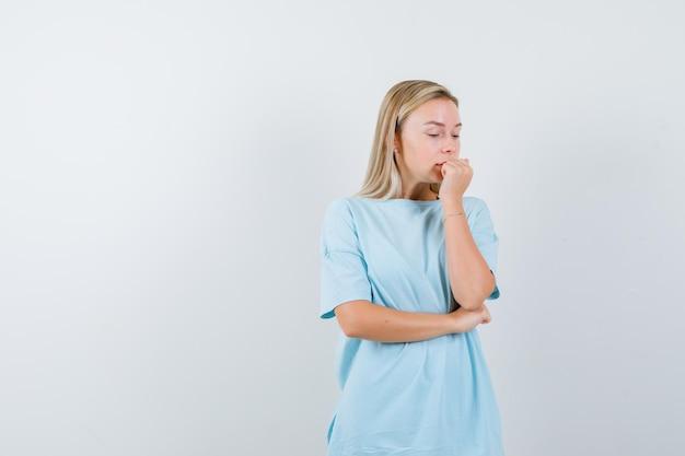 青いtシャツを着た金髪の女性が拳を噛み、肘の下で手を握り、不安そうに見える
