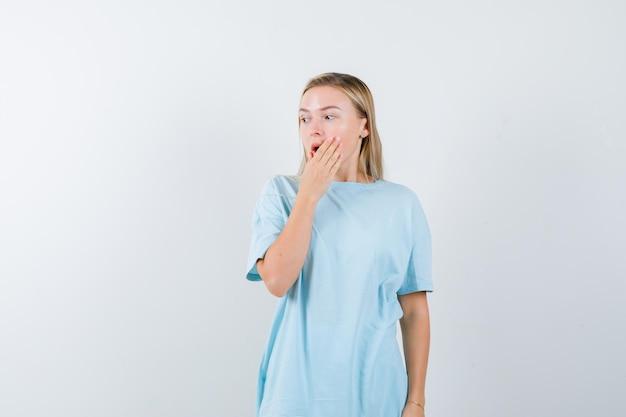 손으로 입을 덮고, 멀리보고 놀란 찾고 파란색 티셔츠에 금발의 여자