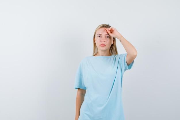 Блондинка в синей футболке держит руку над головой и выглядит серьезно