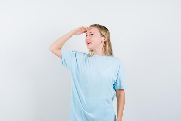 青いtシャツを着た金髪の女性が頭上に手を渡して遠くを見て、集中して見える