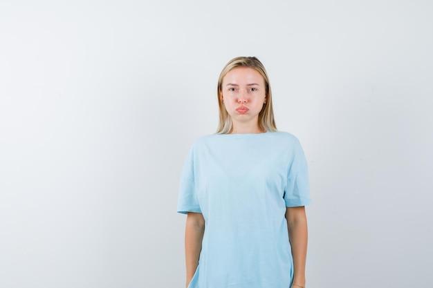 ポーズをとって失望しているように見える間頬を膨らませている青いtシャツのブロンドの女性