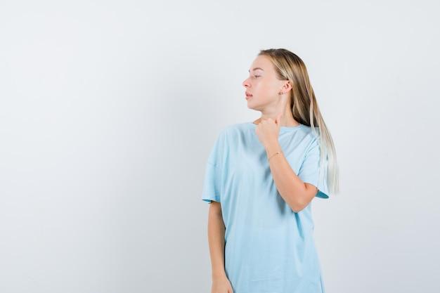 Блондинка в синей футболке показывает большой палец вверх, смотрит в сторону и выглядит красиво