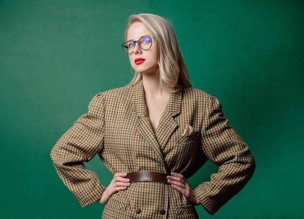 녹색 벽에 영국 스타일 재킷에 금발 여자