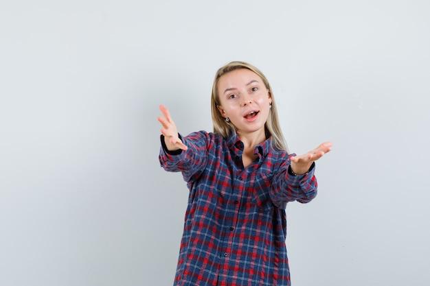 何かを受け取り、楽観的な正面図を見てカメラに向かって手を伸ばしているチェックシャツのブロンドの女性。