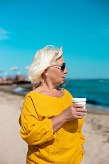 Блондинка в хлопковой блузке держит бумажный стаканчик с кофейным напитком во время прогулки по пляжу