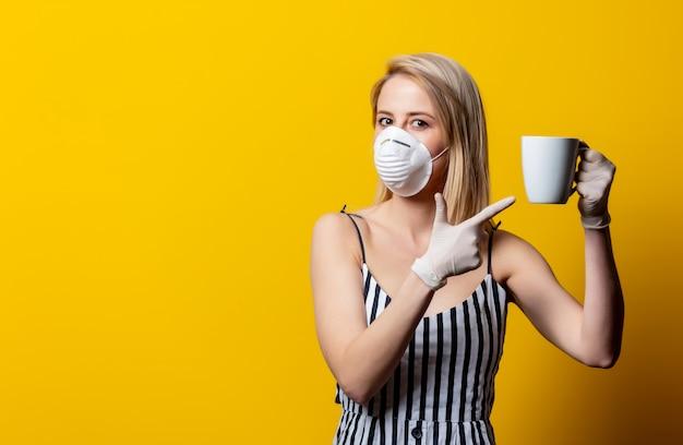 フェイスマスクと手袋で金髪の女性が一杯のコーヒーを保持しています。