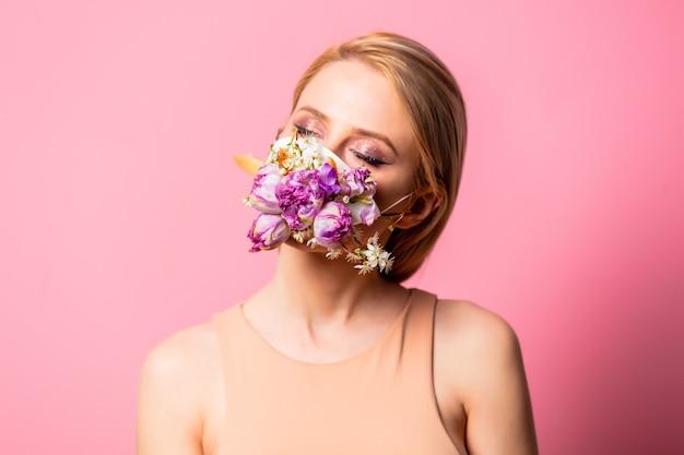 분홍색 배경에 꽃과 얼굴 마스크에 금발 여자