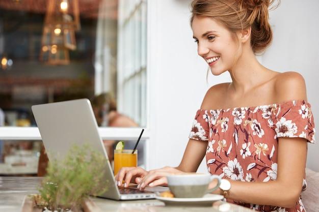 Блондинка в цветочном платье в кафе