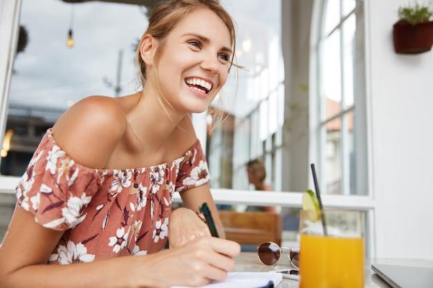カフェで花柄のドレスで金髪の女性