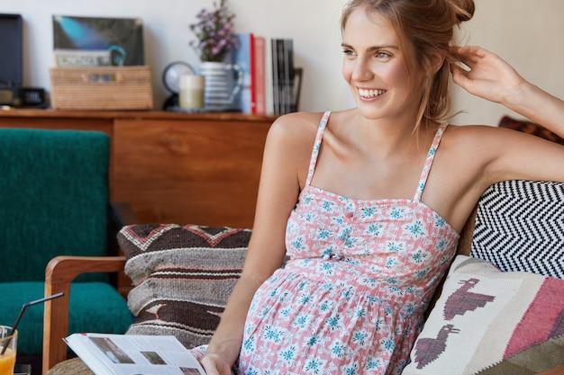 ソファに座っている花柄のドレスで金髪の女性