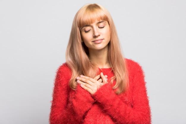 ふわふわの赤いセーターを着た金髪の女性は、心臓の近くの胸に両手のひらを保ちます。気持ち、優しさ。