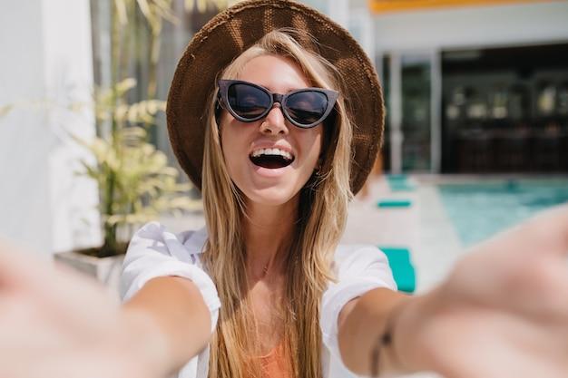 긍정적 인 감정을 표현하는 매력적인 선글라스에 금발 여자. 리조트에서 셀카를 만드는 흥분된 백인 여자의 야외 촬영.